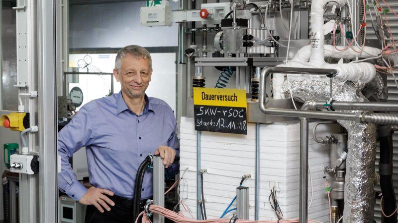 Prof. Blum zeigt am Forschungszentrum Jülich das Herzstück der reversiblen Hochtemperaturanlage:  Sie kann nicht nur aus Wasserstoff Strom erzeugen,  sondern auch umgekehrt aus Strom und Wasserdampf Wasserstoff produzieren.