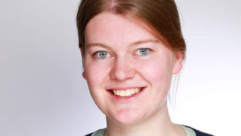 Portraitbild von Theresa Overbeck. Sie hat dunkelblonde Haare und ein freundliches Gesicht.